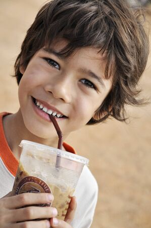 boy 12 year old: Smiling boy drinking iced cocoa LANG_EVOIMAGES