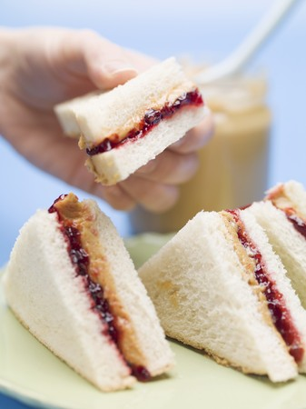 peanut butter and jelly: Hand holding peanut butter and jelly sandwich