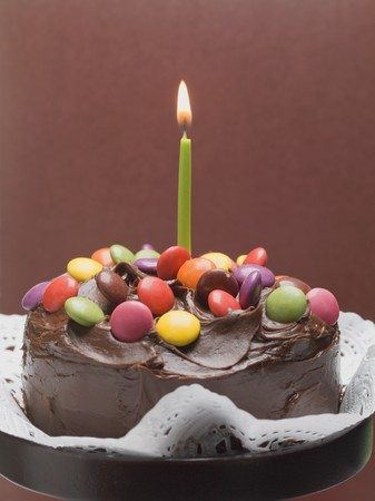 doiley: Chocolate cake with coloured chocolate beans and candle