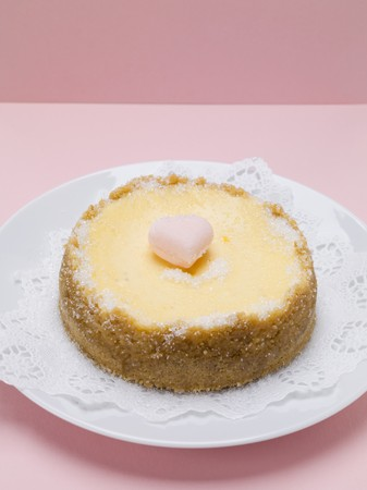 doiley: Small cheesecake with sugar heart on plate with doily LANG_EVOIMAGES