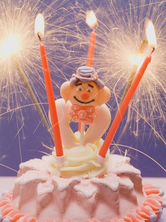 childs birthday party: Small cake with clown & sparklers for childs birthday LANG_EVOIMAGES