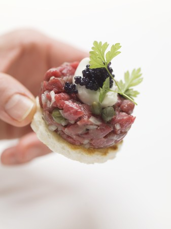tunafish: Hand reaching for tuna tartare canap� LANG_EVOIMAGES