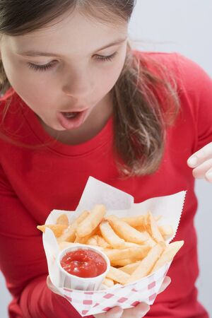 waist deep: Girl holding chips with ketchup