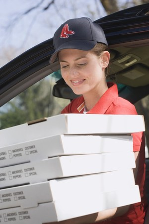 25 to 30 year olds: Woman in baseball cap delivering five boxes of fresh pizza LANG_EVOIMAGES