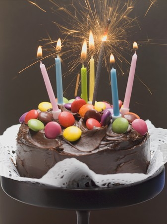 doiley: Chocolate cake with coloured chocolate beans and candles