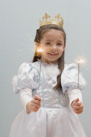 childs birthday party: Little girl dressed as princess holding sparklers LANG_EVOIMAGES