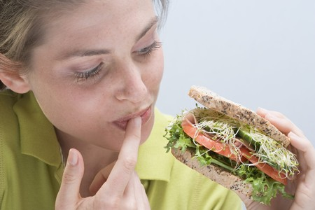 licking finger: Young woman holding sandwich and licking her finger