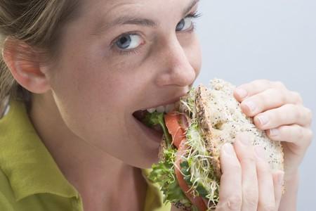 multi grain sandwich: Woman biting into a sandwich with enjoyment LANG_EVOIMAGES