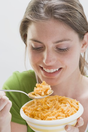 25 to 30 year olds: Young woman with pasta on spoon