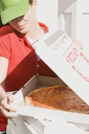 pizza box: Mujer en la visera buscando en la caja de la pizza abierto