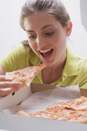 25 to 30 year olds: Young woman eating pizza