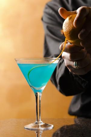 barkeep: Bartender Adding Orange Rind Garnish to Blue Cocktail