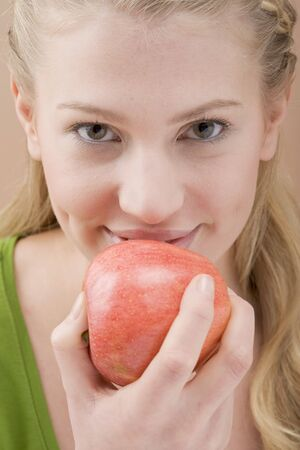 20 to 25 year olds: Woman eating red apple LANG_EVOIMAGES