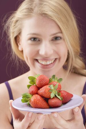 20 to 25 year olds: Woman holding a plate of strawberries LANG_EVOIMAGES