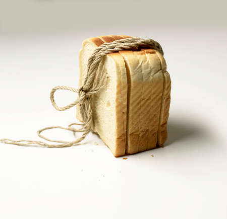 string together: Slices of white bread tied together with string