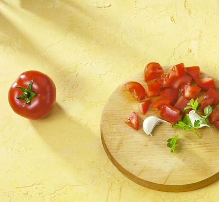 petroselinum sativum: Diced tomatoes, garlic & parsley on chopping board, whole tomato