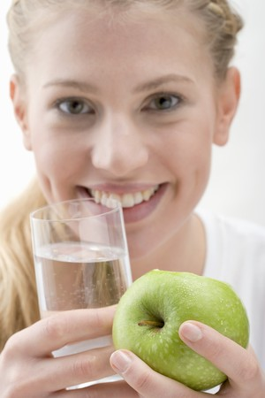 well beings: Woman holding apple and glass of water