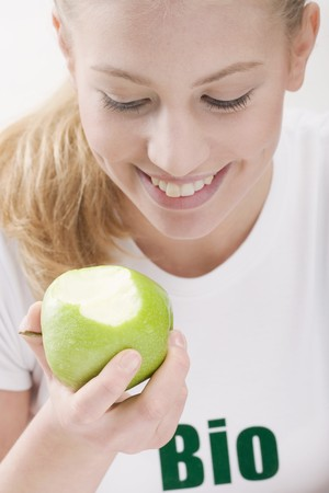 well beings: Woman eating an organic green apple