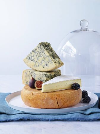 Various cheeses on cheese platter with figs, blackberries