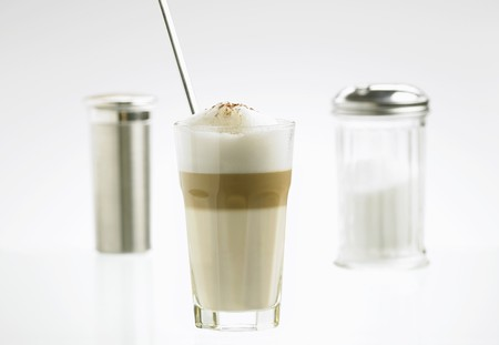 glass topped: A glass of latte macchiato with sugar and cocoa shakers