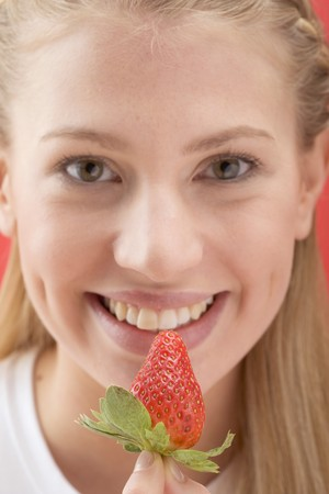 20 to 25 year olds: Woman holding a strawberry