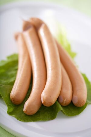 scalded sausage: Five frankfurters on a lettuce leaf