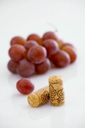 in twos: Two wine corks with red grapes