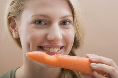 25 to 30 year olds: Woman holding a carrot with a bite taken