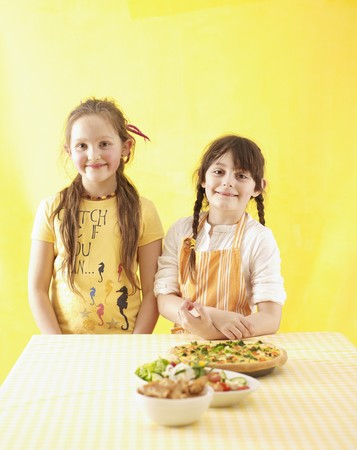 10 to 12 year olds: Two girls standing by kitchen table LANG_EVOIMAGES