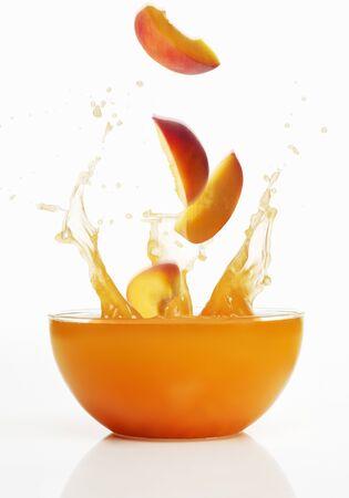 jugo de frutas: Rebanadas del melocot�n que caen en jugo de frutas LANG_EVOIMAGES
