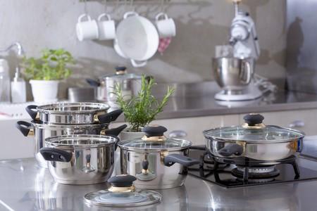 utensilios de cocina: Ollas de acero inoxidable clasificadas en una cocina