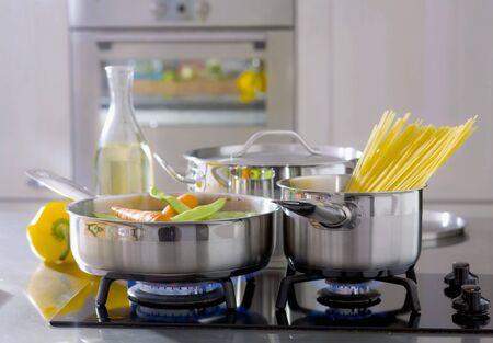 gas cooker: Las verduras y espagueti en sartenes en una cocina de gas
