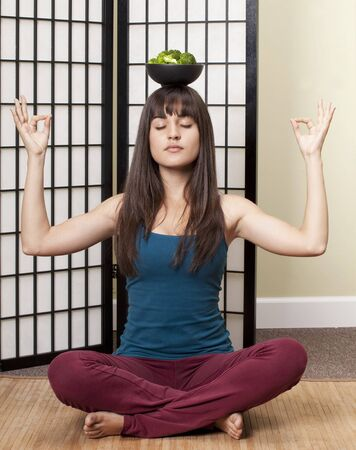 16 to 17 year olds: Girl in Yoga Pose Balancing a Bowl of Broccoli on her Head
