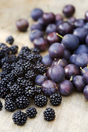brambleberries: Damsons and blackberries on a wooden surface LANG_EVOIMAGES