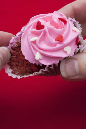 being the case: Taking chocolate cupcake with pink icing out of paper case