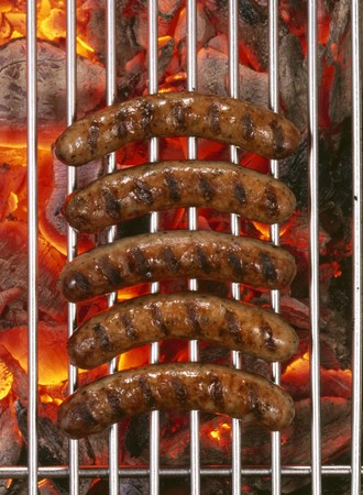 barbecues: Five sausages on barbecue rack over burning charcoal LANG_EVOIMAGES