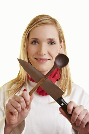25 to 30 year olds: Female chef holding crossed kitchen knife and wooden spoon