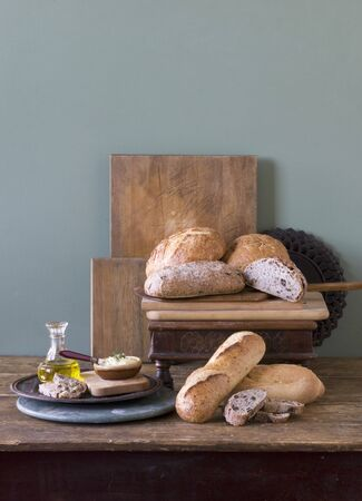 several breads: Rustic Loaves of Bread on Wooden Table with Spreads LANG_EVOIMAGES