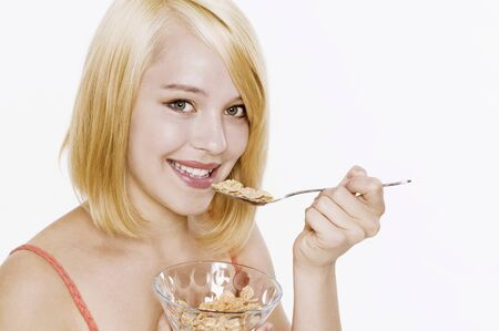 25 to 30 year olds: Woman with blond hair eating cornflakes