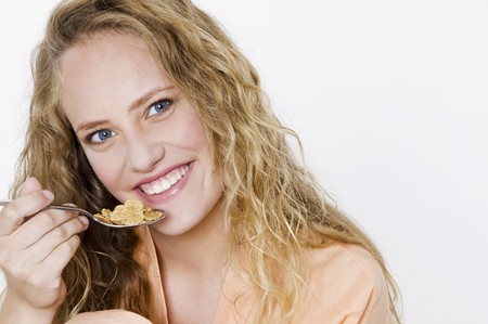 25 to 30 year olds: Young woman eating a spoonful of cornflakes
