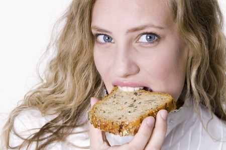 25 to 30 year olds: Young woman bitung into a slice of grannary bread