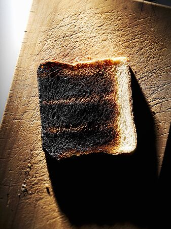 burnt toast: Burnt toast on a wooden board