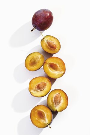 halved: Plums, whole and halved