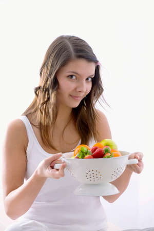well beings: Girl holding a kitchen sieve with fresh fruit