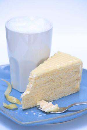 cream on cake: Un gran vaso de caf� con leche y un trozo de lim�n pastel de crema