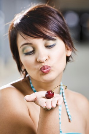 well beings: Young woman with a cherry on her hand LANG_EVOIMAGES