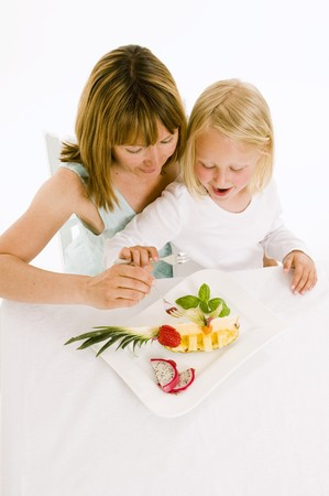 35 to 40 year olds: Mother and daughter eating fruit from plate
