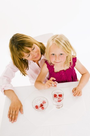 35 to 40 year olds: Mother and daughter, daughter holding a raspberry ice cube