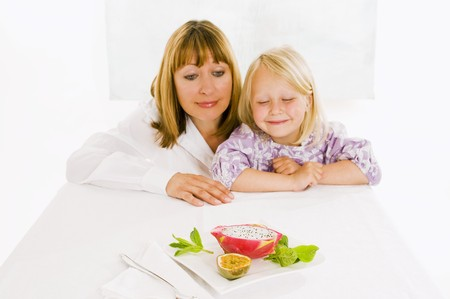 well beings: Mother and daughter sitting at table with plate of fruit