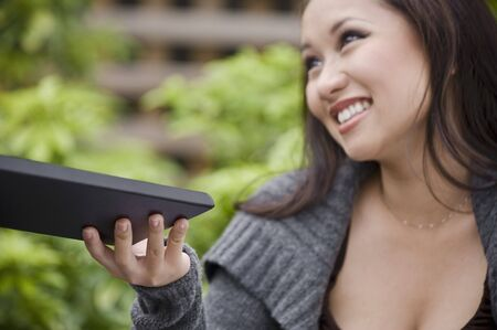 30 to 35 year olds: Young woman holding the menu